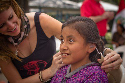 Hilton fits a child in Peru for a hearing aid as part of a Starkey Global Mission. (Courtesy of LSTN)